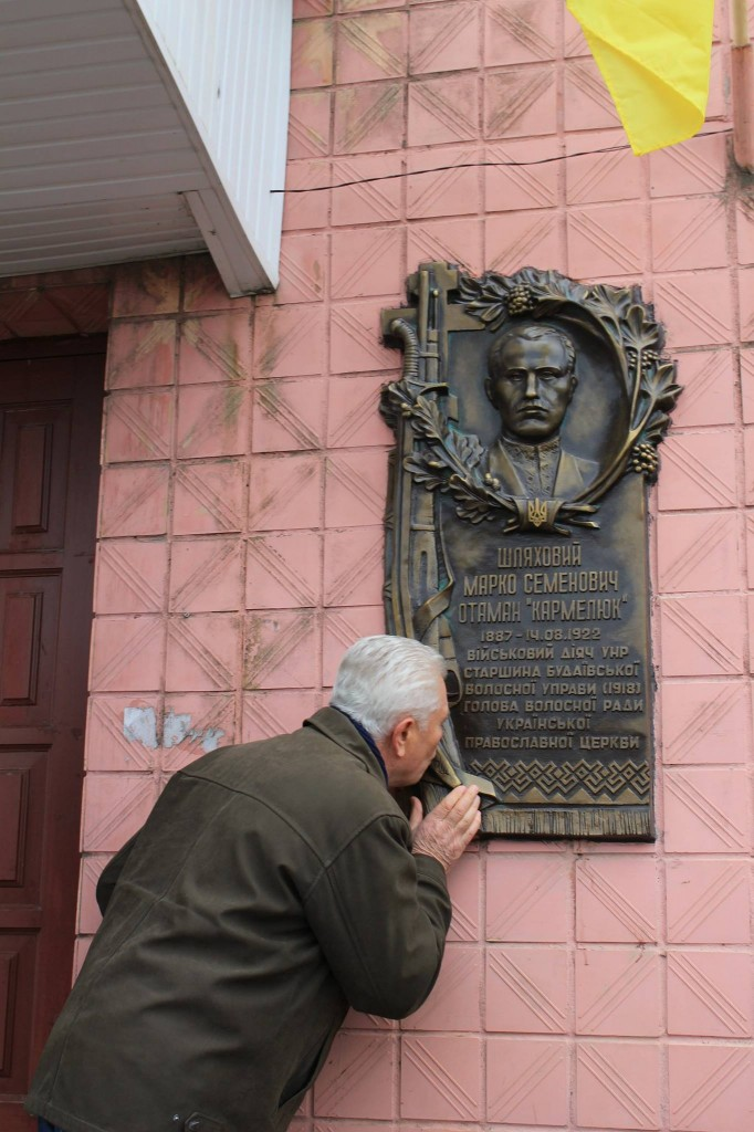 Микола Шляховий, онук Марка Шляхового, цілує меморіальну дошку дідові